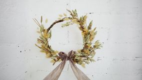 Amazing graceful wreath made from cotton flowers. Beautiful hand made do it yourself wreath from dry flowers and grass and decorated with artisan designer silk stock video
