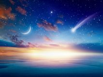 Falling comet, rising crescent moon and stars stock images