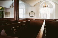 Historic looking Church Building interior with man made wooden pews and Large Glass Windows stock image