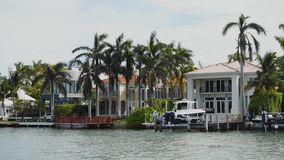 Amazing houses of celebrities among high palm trees with the piers for mooring boats on the shore on star island,sunny. Fashionable mansions of wealthy famous stock video