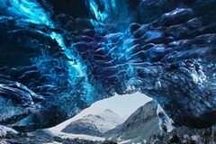 Amazing ice cave. Blue crystal ice cave and an underground river beneath the glacier. Amazing nature of Skaftafell. Amazing ice cave. Blue crystal ice cave and stock images