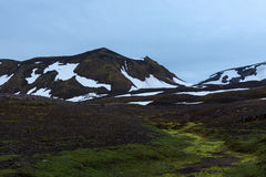 Amazing Iceland green hills with snow patches in. Royalty Free Stock Photography
