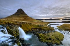 Amazing Icelandic landscape at the top of Kirkjufellsfoss waterfall with Kirkjufell mountain in the background Royalty Free Stock Images
