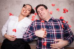 Amazing inlove couple looking at camera while lying on the floor. Next to small red hearts Stock Images