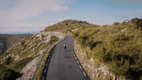 Hipster man rides on skateboard on mountain road. Amazing inspirational epic drone aerial footage of happy excited man riding skateboard in distance on empty stock video