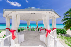 Amazing inviting view of decorated wedding gazebo at tropical beach on blue sky and tranquil ocean background Royalty Free Stock Images