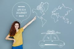 Emotional girl pointing to the map while thinking about travelling. Amazing journey. Cheerful emotional young girl feeling excited while pointing to the map of Stock Images