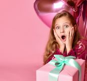Amazed woman holding balloon and gift box over pink background. royalty free stock image