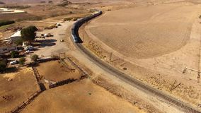 Amazing 4k aerial drone landscape of huge modern urban passenger train moving through dry sand steppe canyon hill desert. Amazing aerial drone landscape of huge stock footage