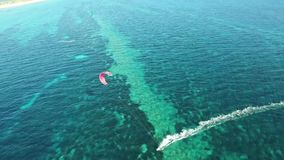 Amazing 4k aerial drone panorama seascape of people kiteboarding in clear blue turquoise ocean water on windy summer day. Amazing aerial drone panorama seascape stock video