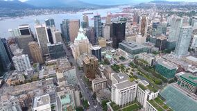 Amazing 4k aerial panorama of tall skyscrapers and towers of Vancouver downtown district bid city skyline by water