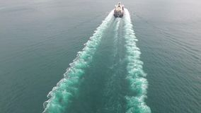 Amazing 4k aerial shot of a cargo container ship sailing away in the ocean waves on a cloudy day stock video footage