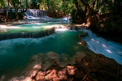 Amazing Kuang Si Falls in Luang Prabang, Laos. Perfect blue water combined with beautiful sunlight and powerful green colors. stock photography