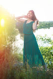 Amazing lady in green long dress posing by river. Amazing full length picture of lady in green long dress posing by river at sunset Stock Photo