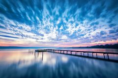 Amazing lake sunset. Magnificent long exposure lake sunset with boat and a wooden pier Royalty Free Stock Photography