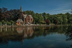 Amazing lake surrounded by greenery and old building. Amazing lake surrounded by greenery and old brick building on the other side in Bruges. With many canals royalty free stock photo