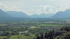 Amazing landscape on green meadows with small houses at base of Alps mountains near Salzburg city stock video footage