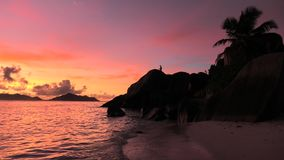 Anse Source d`Argent at dusk. Amazing landscape of huge granite boulders stones and palm trees at entrance to Anse Source d`Argent Beach at dusk in Seychelles stock video footage
