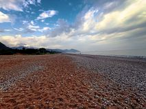 Amazing landscape of mountain near the sea with stone beach and blue sky. Olimpos beach, Turkey.  royalty free stock images
