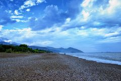 Amazing landscape of mountain near the sea with stone beach and blue sky. Olimpos beach, Turkey.  royalty free stock photography