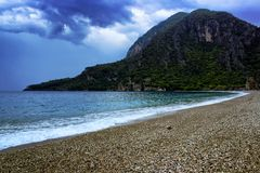 Amazing landscape of mountain near the sea with stone beach and blue sky. Olympos beach, Turkey.  royalty free stock image
