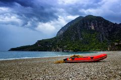 Amazing landscape of mountain with red boat near the sea with stone beach and blue sky. Olympos beach, Turkey.  royalty free stock photography