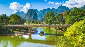 Amazing landscape of river among mountains. Laos. Panorama. Amazing landscape of Nam Song river among mountains. Bridge on the foreground. Pha Tang, Vang Vieng Royalty Free Stock Photography