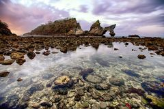 Amazing landscape of rocky arches and water reflection in Bali, Indonesia. This is taken in Bali, Indonesia. It was taking during sunset. There are huge stock images