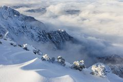 Amazing landscape of rugged mountain ridge raising above the clouds and fog royalty free stock photo