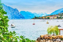 Amazing landscape of shore of Brenzone commune city Lake Garda with mountains, cloudy sky and ships in northern Italy. Veneto regi royalty free stock photography