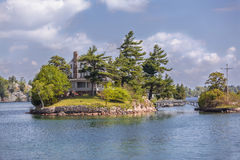 Amazing landscape view of little island with small house standing in the lake Royalty Free Stock Image