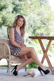 Amazing leggy women with a dog for companionship. Amazing cute and slim leggy woman sitting on wooden chair wearing high heels and short dress revealing her long Royalty Free Stock Photo