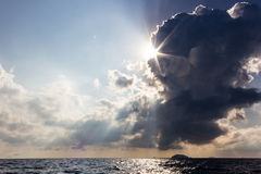 Amazing light breaks through clouds above the sea. Amazing light flare of the sun break through the clouds in the evening above the sea stock photos