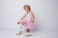 Amazing little ballerina tying pointes in studio Royalty Free Stock Photos