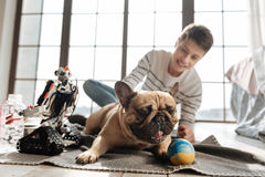 Amazing little dog playing with colorful ball. Give it to me. Thoughtful pug dog showing his tongue lying between robot and his young master while looking Stock Photo