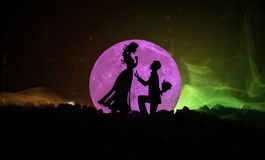 Amazing love scene. Silhouettes of man making proposal to woman or Silhouettes of couple against big moon at background. Selective focus Stock Photo