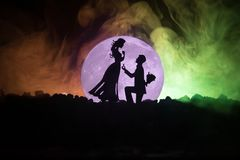 Amazing love scene. Silhouettes of man making proposal to woman or Silhouettes of couple against big moon at background. Selective focus Royalty Free Stock Photo