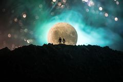 Amazing love scene. Silhouettes of young romantic couple standing under the moon light. Valentine`s day concept stock illustration