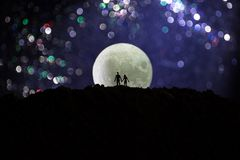 Amazing love scene. Silhouettes of young romantic couple standing under the moon light stock images