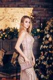 Amazing luxury seductive woman in stylish golden party dress posing on Christmas decoration background stock photo