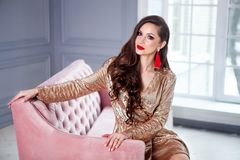 Amazing luxury woman in stylish gold shining party dress sits on a pink sofa . Bright smokey eyes make up, red full lips, healthy stock photo