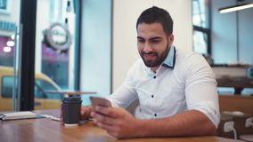 Amazing man holding a cup of coffee, and smiling towards the phone screen. Everyday routine, social networks. Using stock video footage