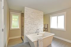 Amazing master bathroom with a freestanding bathtub. Amazing master bathroom accented with stone wall walk-through shower and freestanding bathtub over Porcelain Royalty Free Stock Photo