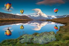 Amazing Matterhorn peak and hot air balloons reflecting in water. Famous Matterhorn peak and Stellisee mountain lake with colorful hot air balloons. Fantastic royalty free stock images