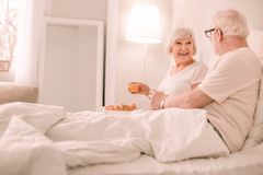 Amazing mature woman having breakfast in bed royalty free stock image