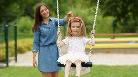 Amazing Mom Wearing Blue Short Dress Spends Time with Her Little Daughter Outdoors. Cute Girl Riding a Swing on the stock footage