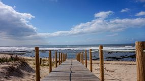 Boardwalk over the sand dunes leading to the sea on a beautiful and relaxing beach morning at Gaia, Porto, Portugal royalty free stock image