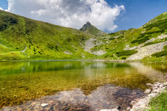Amazing mountain lake and stony peak in summer time Royalty Free Stock Photography