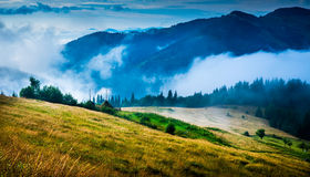 Amazing mountain landscape. With fog and a haystack Royalty Free Stock Images