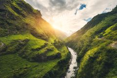 Amazing mountains covered green grass, river at sunset Stock Photos